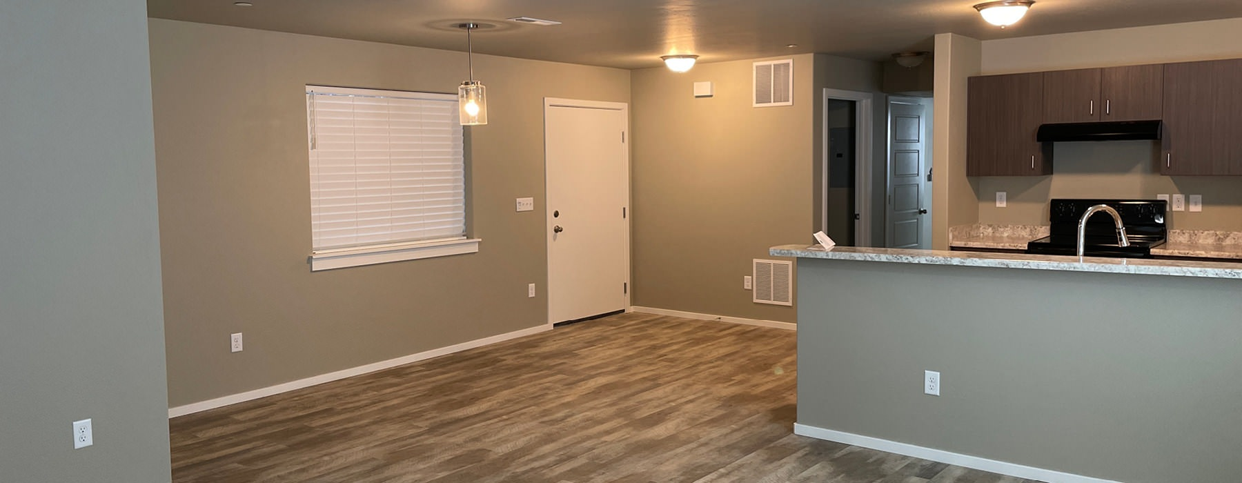 iving room with ceiling fan and light fixture open to kitchen and dining areas