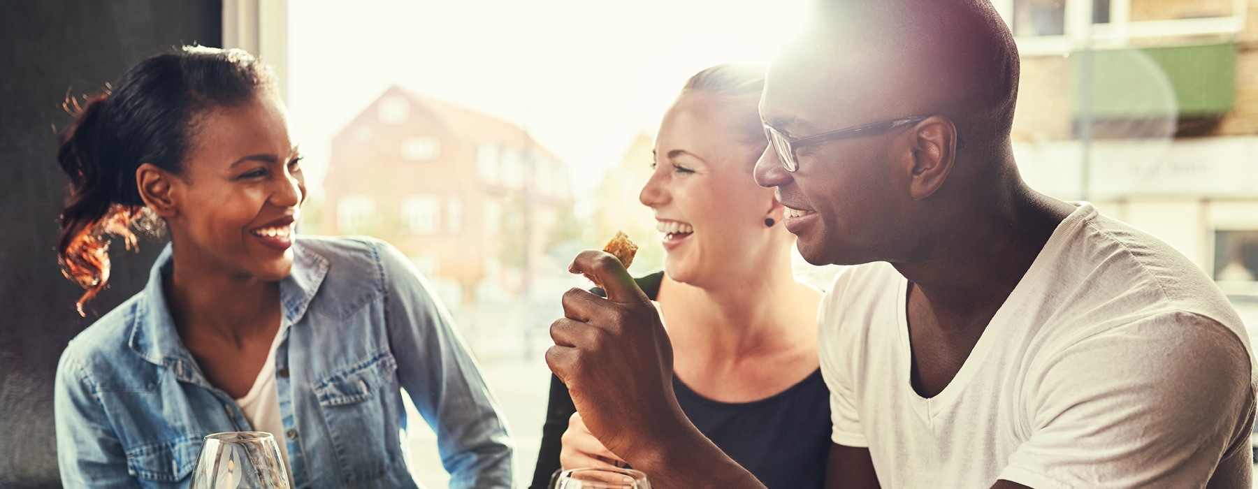 young friends laugh and smile with food and drinks at restaurant