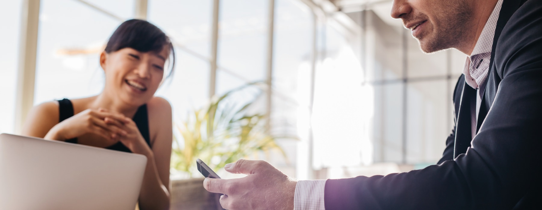 business woman and man with laptop and phone meet in front of large, bright windows